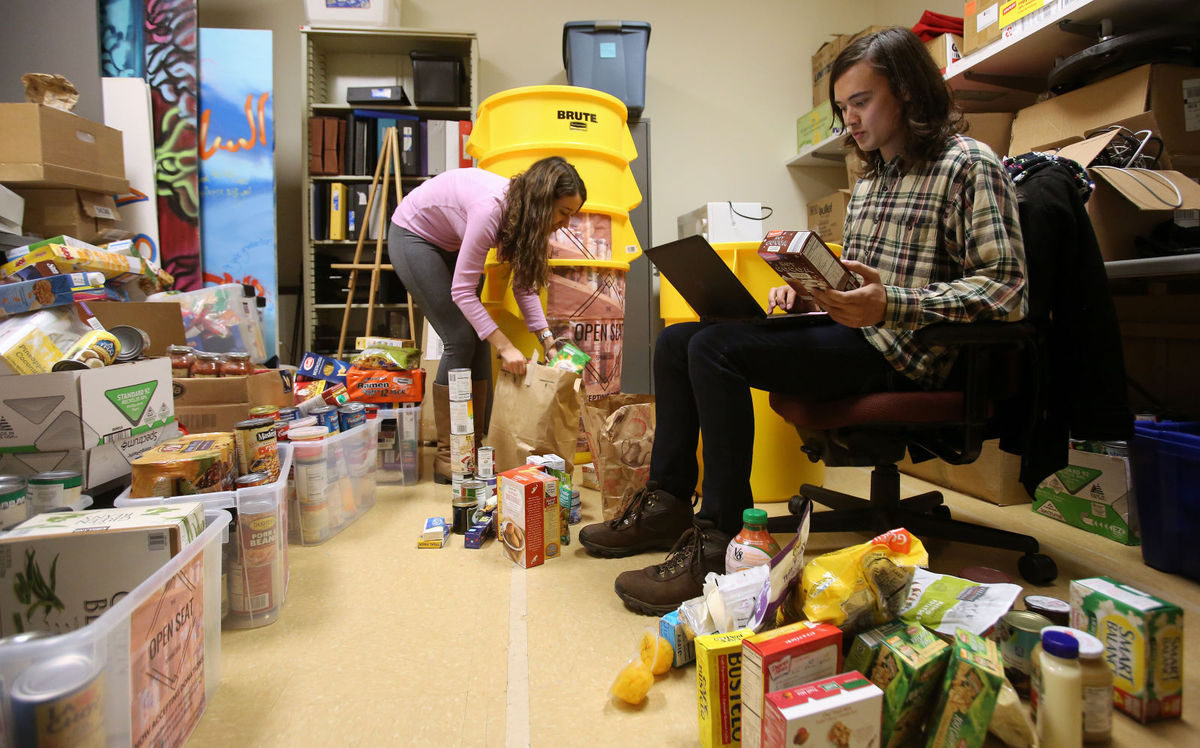 Alison Montenegro (left) and Shane Linden, both sophomores at UW-Madison, take inventory for the Open Seat Food Pantry at UW-Madison.