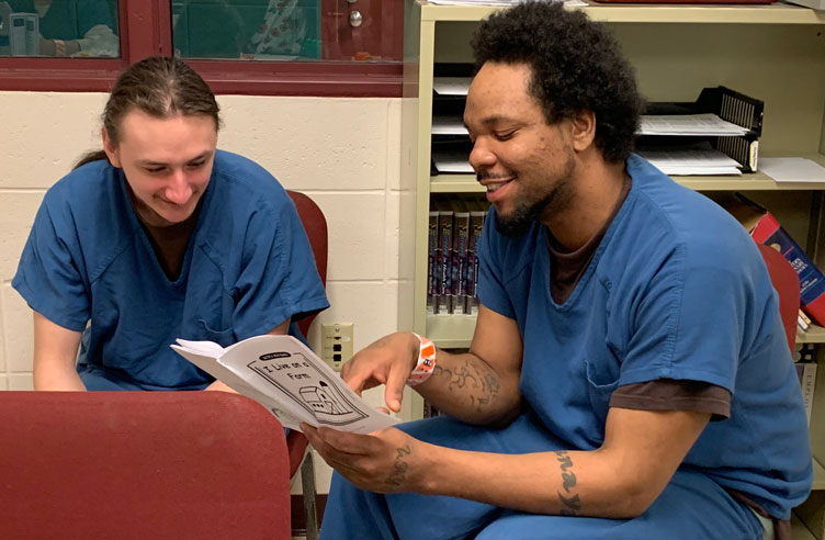 Ben and Cory, dads in the Dane County Jail and Parenting Inside Out students read pamphlet together