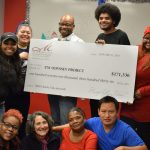 Odyssey's award-winning Director of Development and Community Partnerships, Jenny Pressman poses with Odyssey students holding a giant check
