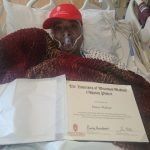Diane lying in a hospital bed wearing a respirator, and holding her Odyssey graduate diploma